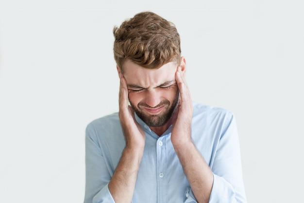 頭痛から苦しむ若い男の混乱