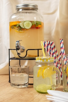 Dispenser of natural drinks with homemade citrus juice on a wooden surface, different types of glasses and jugs with sorbet and ice