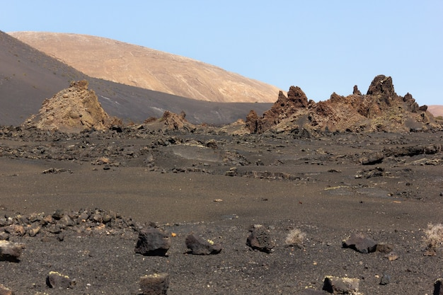 Lanzarote, canary islands의 timanfaya 자연 공원에서 화산 지형의 바위를 분산하십시오.
