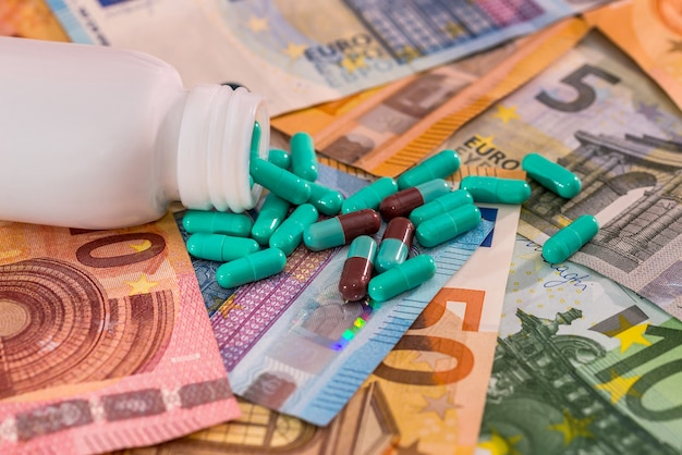 Dispersed pills from bottle on euro banknotes