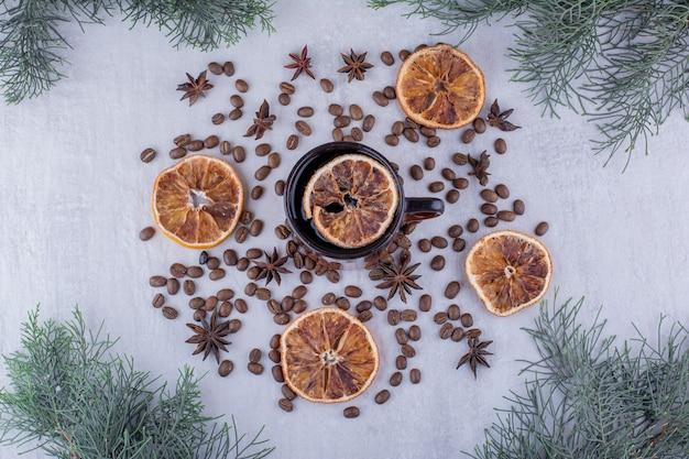 Visualizzazione di semi di anice, fette d'arancia essiccate e una tazza di tè su sfondo bianco.
