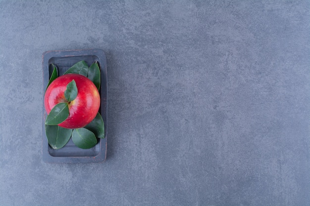 A display of apple on a wooden plate on the dark surface