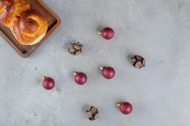 Display of christmas balls and a sweet bun on marble table.