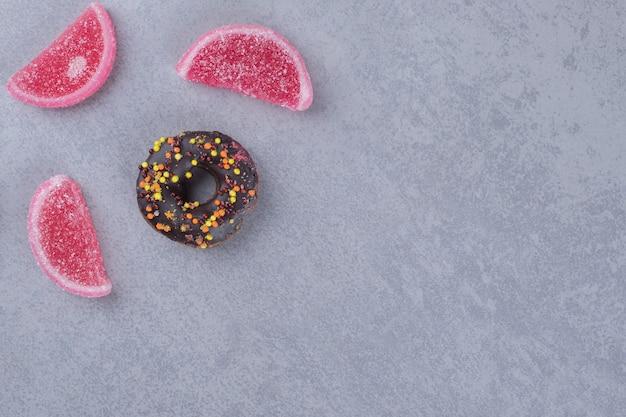 Отображение небольшого пончика и трех мармеладов на мраморной поверхности