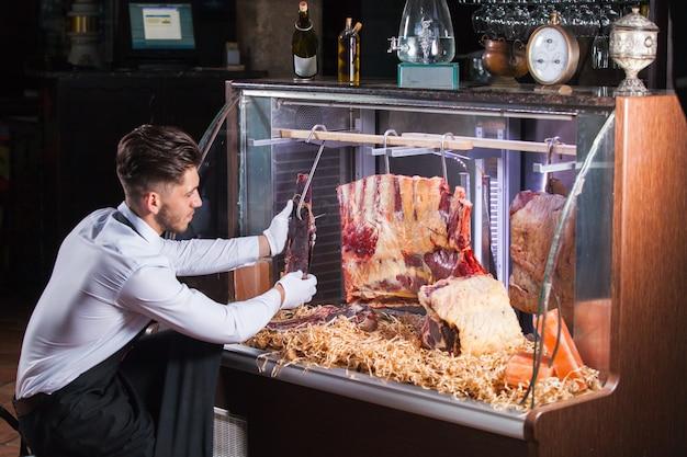 Дисплей сухого выдержанного мяса стейки в мясной лавке или ресторане в витрине холодильника.