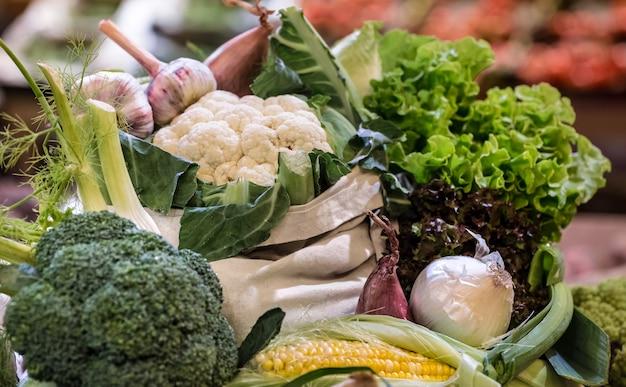 週末のファーマーズマーケットでの新鮮な熟した有機ブロッコリー、綿の袋に入った緑と野菜のサラダの展示
