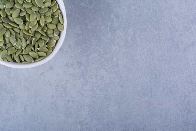 Un display di semi di zucca in una ciotola sulla superficie di marmo