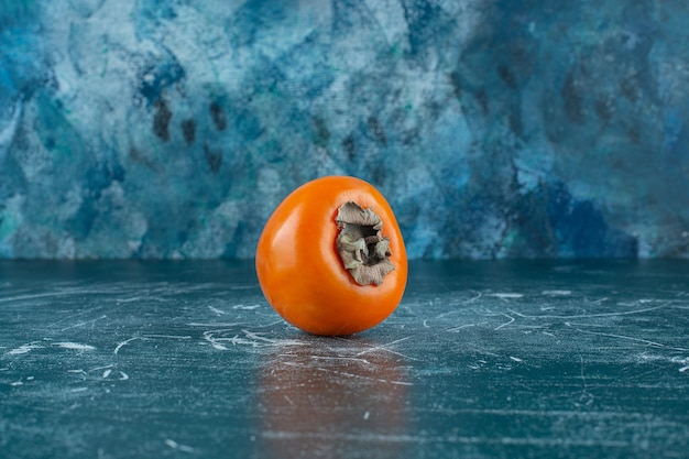 A display of ripe persimmon , on the marble table.