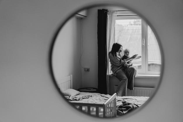 Отображение в зеркале того, как мать играет со своим ребенком. мать грудного ребенка. счастливое материнство. семья дома. портрет счастливой матери и ребенка.