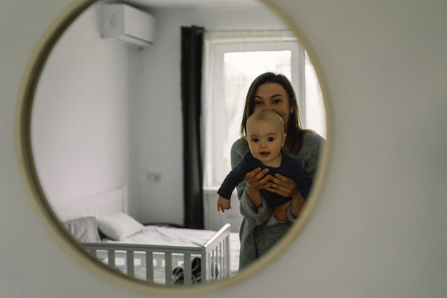 Displaying in the mirror how a mother plays with her child. mother of a nursing baby. happy motherhood. the family is at home. portrait of a happy mother and child.