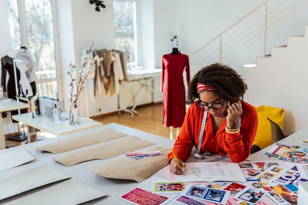 紙に表示する。新しいルックスを発明するインスピレーション作品に囲まれた思いやりのあるアフリカ系アメリカ人デザイナー