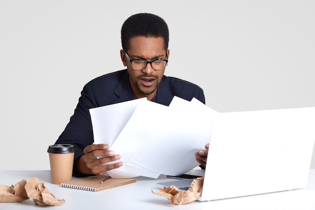 Displeased african american man looks with puzzlement at paper documents, has deadline to prepare financial report, sits at destop agaist white wall, works on laptop computer. paperwork