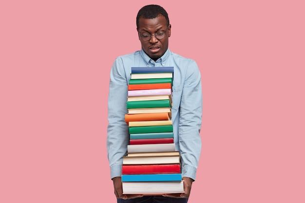 Lo scienziato o studente afroamericano dispiaciuto trasporta una pesante pila di libri di testo, indossa una camicia elegante