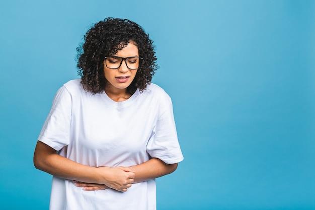불쾌한 아프리카 계 미국인 여성은 위장에 불편 함을 느끼고 손바닥을 배에 유지하고 생리통이 있으며 캐주얼 티셔츠를 입고 버릇없는 음식을 파란색 배경에 격리합니다.