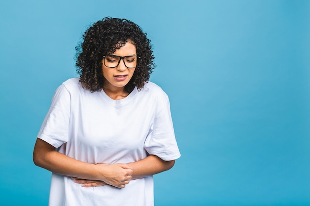 Displeased african american woman feels discomfort in stomach, keeps palms on tummy, has period cramps, wears casual t shirt, spoiled food, isolated on blue background.