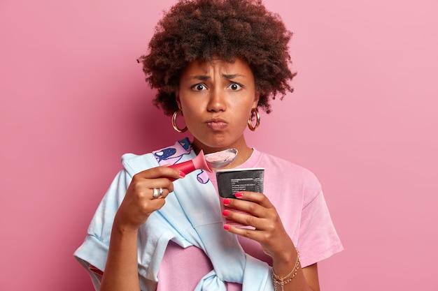 La donna afroamericana scontenta ha denti sensibili, mangia gelato molto freddo, aggrotta le sopracciglia per sentimenti spiacevoli in bocca, posa con dessert congelato, trascorre il tempo libero durante le calde giornate estive