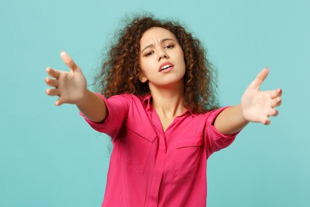 スタジオで青いターコイズブルーの壁の背景に分離された手を伸ばして立っているピンクのカジュアルな服を着た不機嫌なアフリカの女の子。人々の誠実な感情、ライフスタイルのコンセプト。コピースペースをモックアップします。