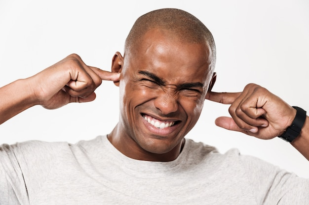 Displeased african man closes ears from a noise.