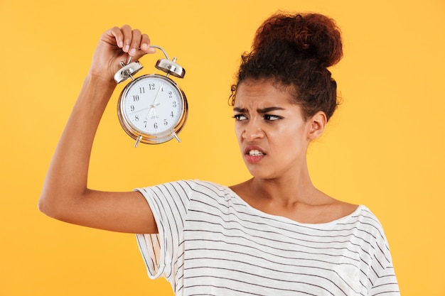 Displeased african woman holding alarm clock and looking on them