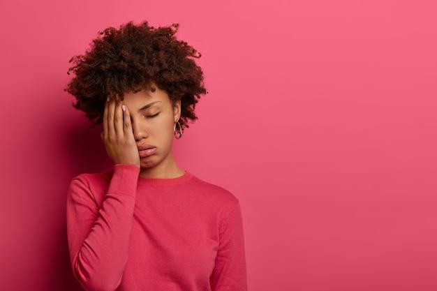 不機嫌なアフリカ系アメリカ人の女性は、手のひらで顔を覆い、非常に疲れて疲れを感じ、仕事を続けることができません
