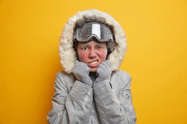 La donna afroamericana dispiaciuta ha la faccia coperta di ghiaccio stringe i denti dal freddo sembra infelice indossa giacca e occhiali da sci gode di vacanze estive trema durante il gelo