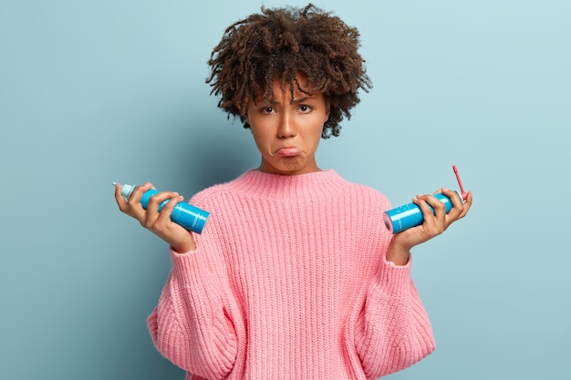 Displeased afro american woman purses lower lip, holds two bottles of aerosol, cures herself