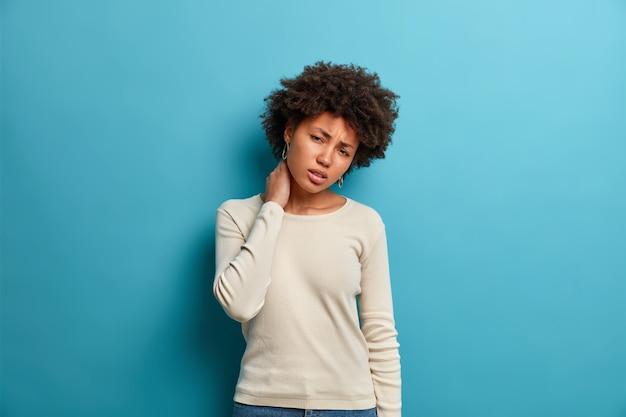 不機嫌なアフリカ系アメリカ人の女性が首に触れる