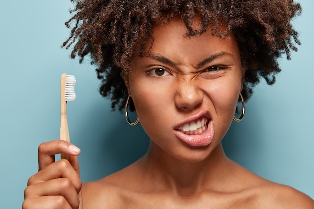 Displeased afro woman frowns face, clenches teeth, takes care of oral hygiene, has curly hair, holds toothbrush, demonstrates bare shoulders, poses over blue wall.