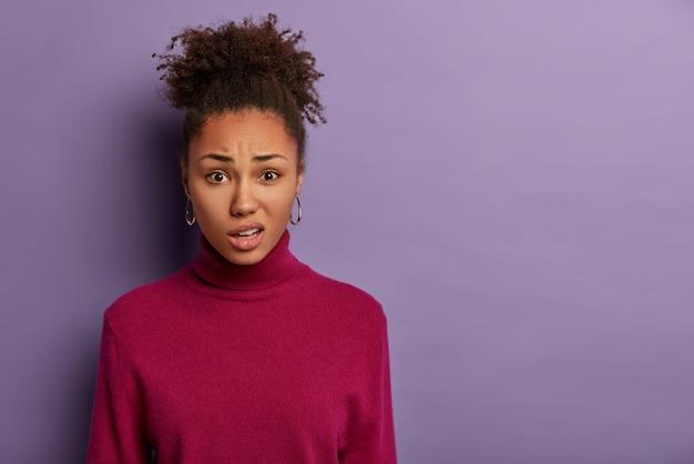 La donna afro dispiaciuta fa un sorrisetto e stringe le labbra, reagisce quando sente qualcosa di spiacevole