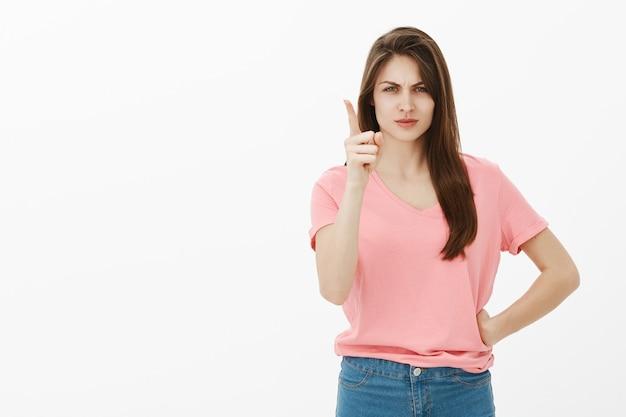 スタジオでポーズをとって不機嫌で怒っているブルネットの女性