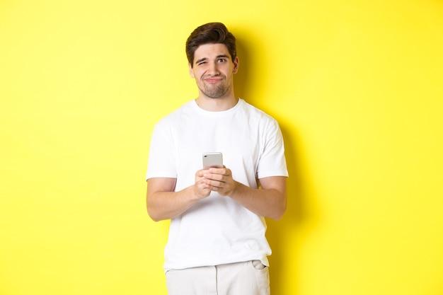 不機嫌で嫌がる男が顔をゆがめ、スマートフォンのメッセージに面白がらず、黄色の背景の上に立っている