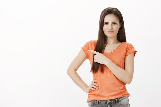 Недовольная и дутая милая девушка жалуется, указывая пальцем в левый верхний угол