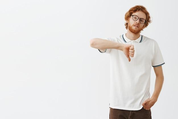 Недовольный и расстроенный бородатый рыжий парень позирует на фоне белой стены в очках