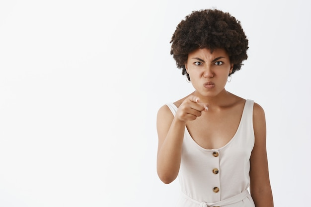 Displeased angry and disappointed dark-skinned wife with afro hairstyle, pointing with index finger, frowning, pulling face from anger, being outraged on someone