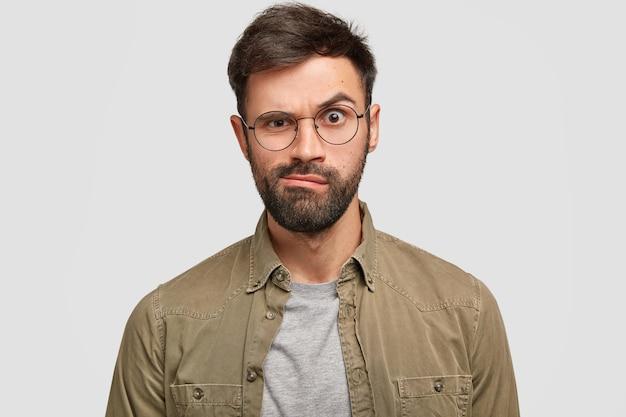Uomo europeo arrabbiato scontento solleva le sopracciglia e porta furiosamente le labbra, vestito con una camicia alla moda, esprime emozioni negative, isolato sopra il muro bianco. concetto di espressioni facciali