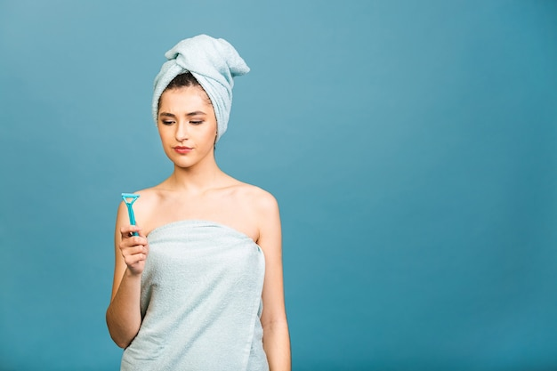Недовольная злая женщина против бритья, держит в руке бритву, поддерживает восковую депиляцию, позирует полуобнаженной, показывает обнаженные плечи