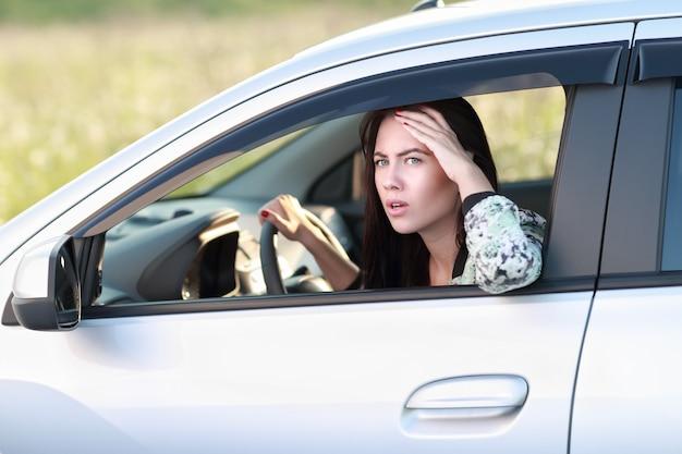 그녀의 차를 운전하는 불쾌한 화난 여자 부정적인 인간의 표정.