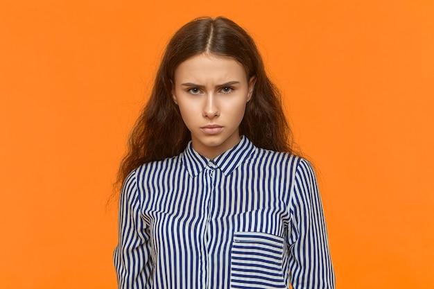 Giovane donna dai capelli scura caucasica arrabbiata dispiaciuta che ha espressione facciale scontrosa scontrosa