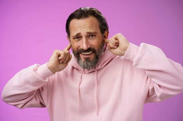 不快なイライラした大人のあごひげを生やした男は、不快感を感じて気を散らし、大声でひどい音をしかめ、しわがれ声を上げます。