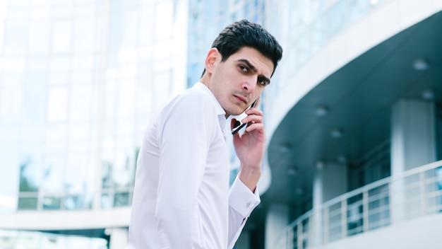 不機嫌そうなしかめっ面のビジネスマン。重要な電話中に気が散る。都市の背景。忙しいライフスタイル