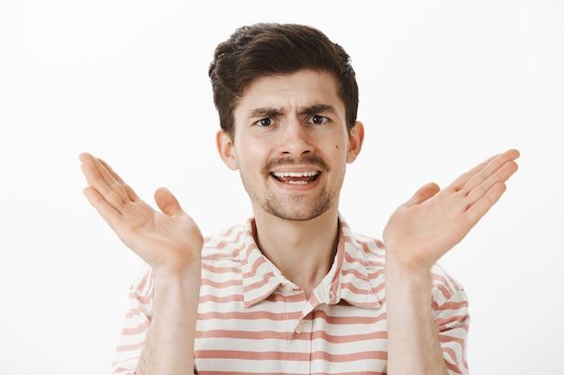 Недовольный раздраженный обыкновенный мужчина европеоидной расы с усами, поднимающий ладонь перед лицом и спорящий, недовольный и разочарованный, слышащий чушь над серой стеной