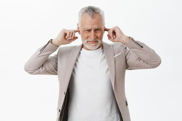 不快なイライラした年配の男性が耳を閉じ、ひどい騒音から顔をしかめる