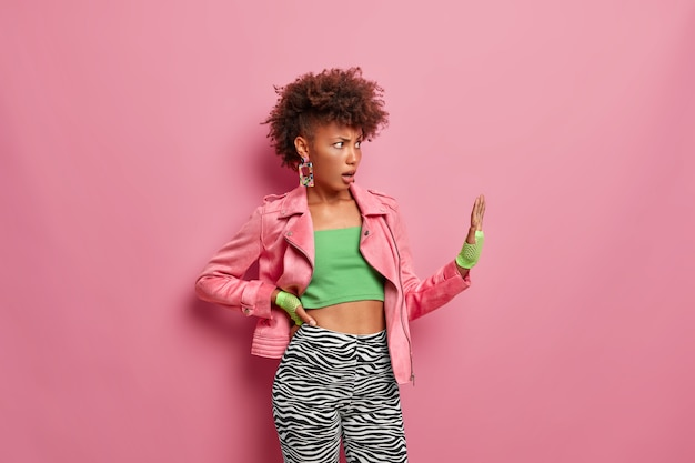 Displeased annoyed woman makes stop gesture, keeps palm forward in refusal gesture, asks not come closer, dressed in stylish sportswear