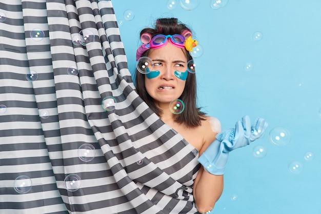 불쾌한 성가신 젊은 아시아 여성이 위생과 미용 치료를 받고 수영 고글을 착용하고 고무 장갑을 착용하고 샤워 커튼 뒤에 알몸을 숨 깁니다.