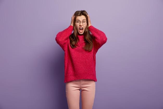La giovane donna infastidita scontenta grida con rabbia, tiene le mani sulla testa, esprime emozioni negative, indossa occhiali rotondi, maglione rosso, irritata per qualcosa di brutto, isolato su un muro viola