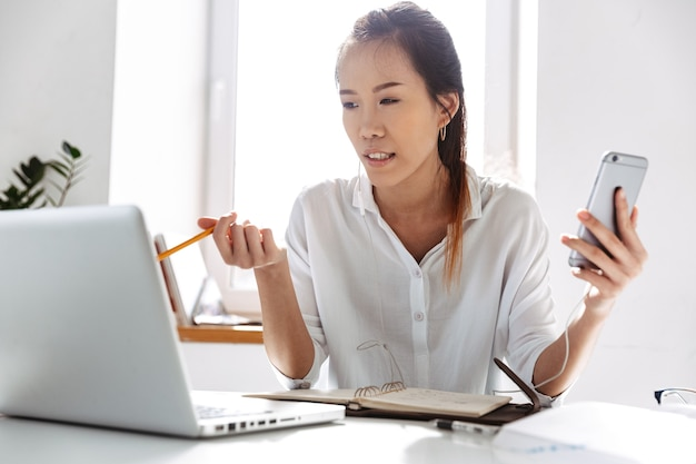 Displeased asian business woman using smartphone and laptop computer while sitting by the table in office