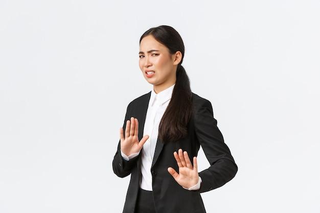 불쾌한 아시아 여성 사업가는 위험한 제안을 피하고, 거절하며 악수하고, 역겨운 이상한 제안을 거부합니다. 혐오감에서 찡그린 판매원과 멀리, 흰색 배경