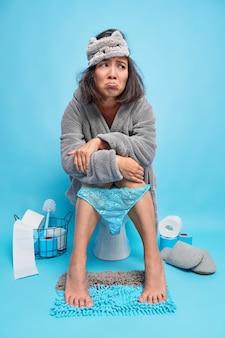 Недовольная азиатская женщина чувствует себя несчастной и сонной после раннего пробуждения, носит халат с маской для сна и кружевные штаны, натянутые на ноги, позирует в туалете на унитазе синяя стена страдает от диареи