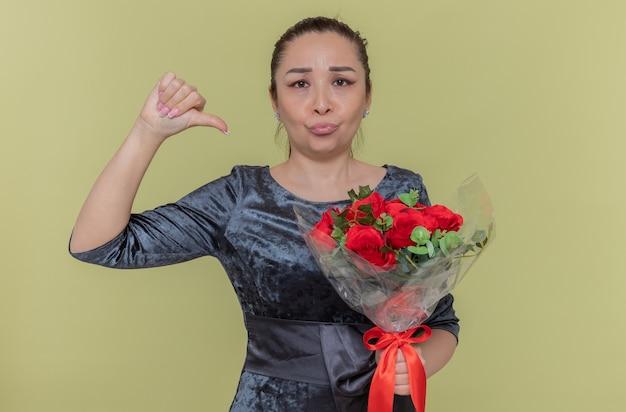 Недовольная азиатская женщина, держащая букет красных роз, глядя вперед, показывая большой палец вниз, празднует международный женский день, стоя у зеленой стены