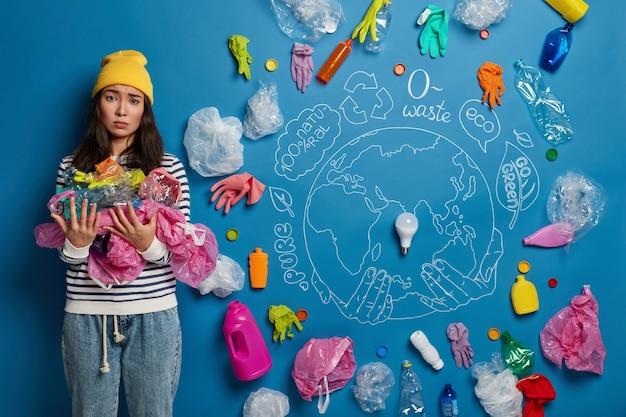 Donna asiatica scontenta raccoglie i rifiuti, aggrotta le sopracciglia per lo scollegamento, essendo ecologicamente amichevole, salva la terra dalla contaminazione, chiede di smettere di distruggere il nostro pianeta